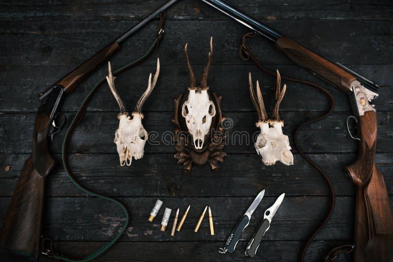 Fachowy myśliwego wyposażenie dla tropić Karabin, noże, trofeów sculps, amunicje i inny na drewnianym czarnym tle, Tro zdjęcia royalty free