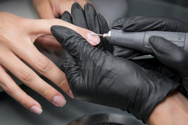 Fachowy narzędzia pedicure używać elektryczną maszynę Manicurzysta grinded gwoździe dziewczyna w gwoździa salonie obrazy stock