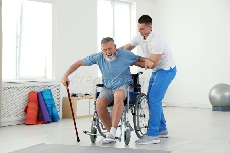 Fachowy physiotherapist pracuje z starszym pacjentem zdjęcia royalty free