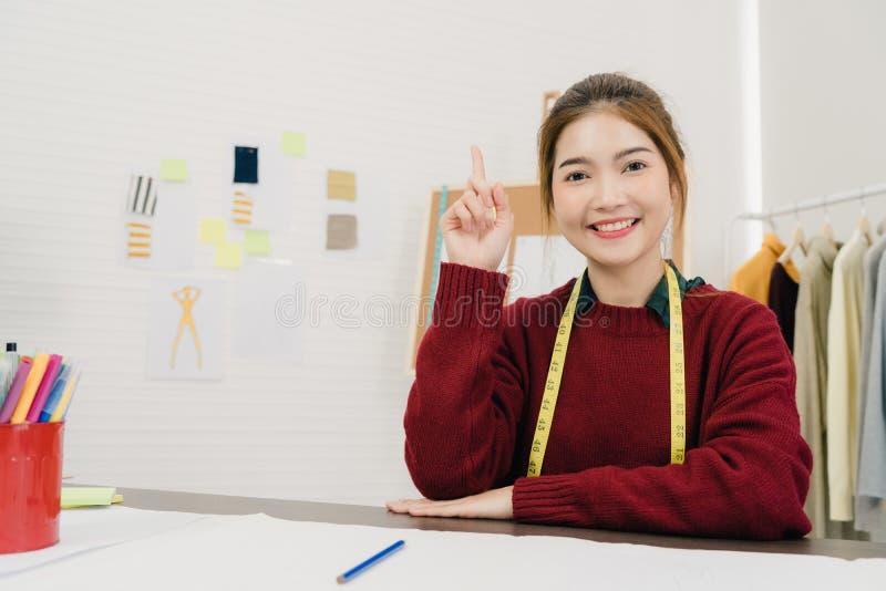 Fachowy piękny Azjatycki żeński projektant mody pracuje z tkanin nakreśleniami i rysunkowym odzież projektem przy studiiem fotografia stock
