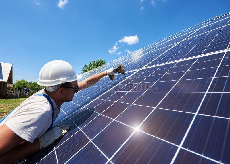 Fachowy pracownik instaluje panel słoneczny na zielonej metal budowie zdjęcia stock