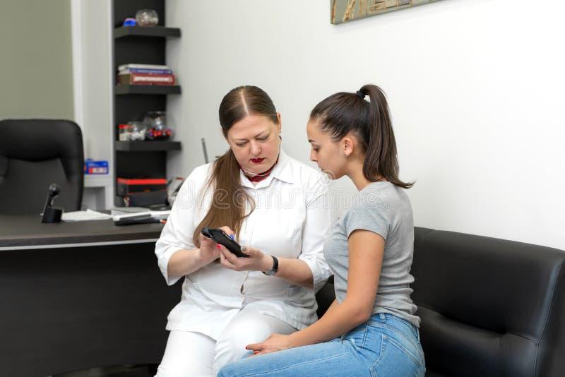 Fachowy pralniany dermatolog dyskutuje obrazki jej gramocząsteczki z cyfrowym dermatoscope z pacjentem zdjęcie royalty free