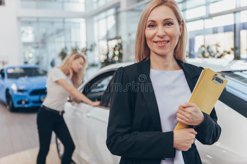 Fachowy samochodowy handlowiec pomaga jej żeńskiego klienta fotografia royalty free