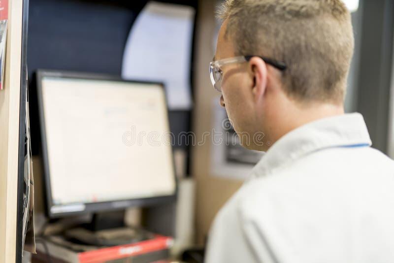 Fachowy samochodowy mechanik pracuje w auto remontowej usługa używać komputer obraz stock