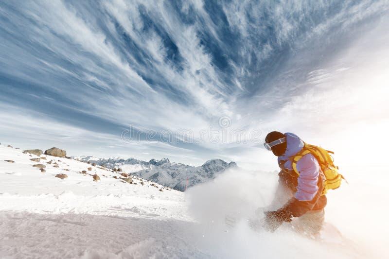 Fachowy snowboarder z plecakiem opuszcza chmurę śnieżny proszek przy zmierzchem na tle epopei chmury i zdjęcia stock