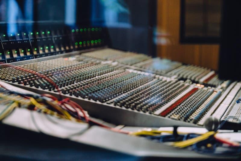 Fachowy soundboard wliczając audio melanżeru pulpit operatora z guzikami, suwaki, sznury i mikrofon w studio nagrań, obrazy stock