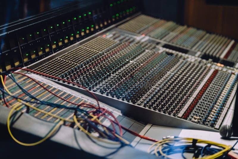 Fachowy soundboard wliczając audio melanżeru pulpit operatora z guzikami, suwaki, sznury i mikrofon w studio nagrań, zdjęcie stock