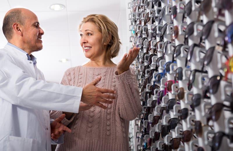 Fachowy sprzedawca jest mężczyzna doradza Dojrzałej blondynki blisko pokazów okularów przeciwsłonecznych optyka klient fotografia stock