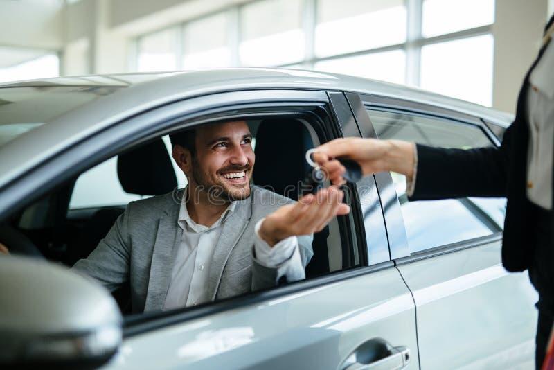 Fachowy sprzedawca podczas pracy z klientem przy przedstawicielstwem firmy samochodowej Dawać kluczom nowy właściciel samochodu obrazy stock