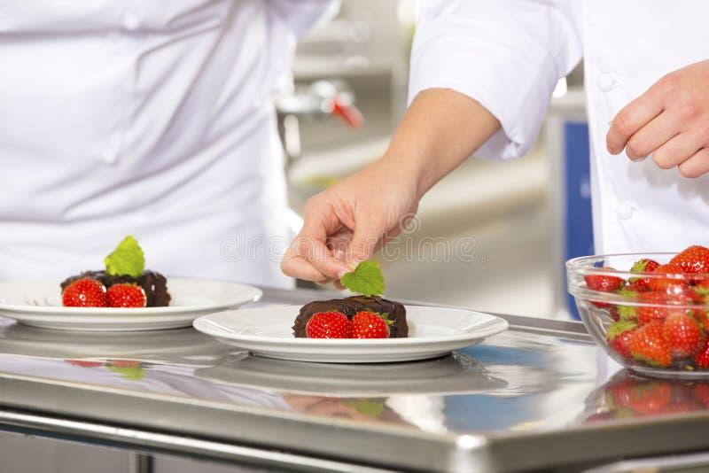 Fachowy szef kuchni dekoruje deseru tort z truskawką zdjęcia stock