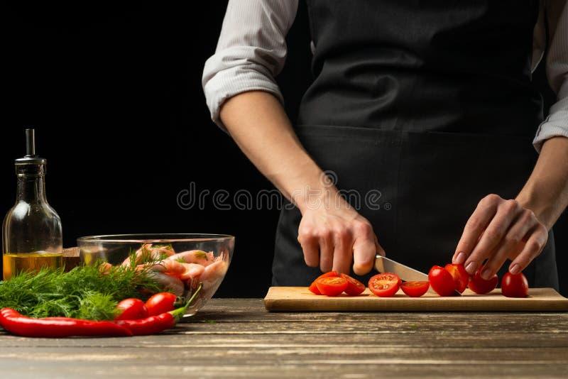 Fachowy szef kuchni pokrajać czereśniowych pomidory dla garneli z warzywami pojęciem owoce morza i zdrowym jedzeniem, Horyzontaln obraz royalty free