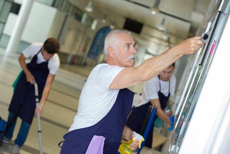 Fachowych czyścicieli drużynowy działanie w budynku obraz royalty free