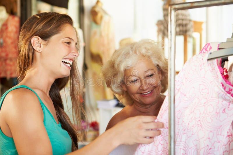 Fachverkäufer, der ältere weibliche Kunden-Kleidung zeigt lizenzfreie stockfotografie