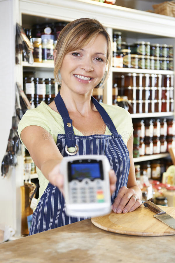 Fachverkäufer im Lebensmittelgeschäft Kreditkarte-Maschine übergebend Cus stockfoto