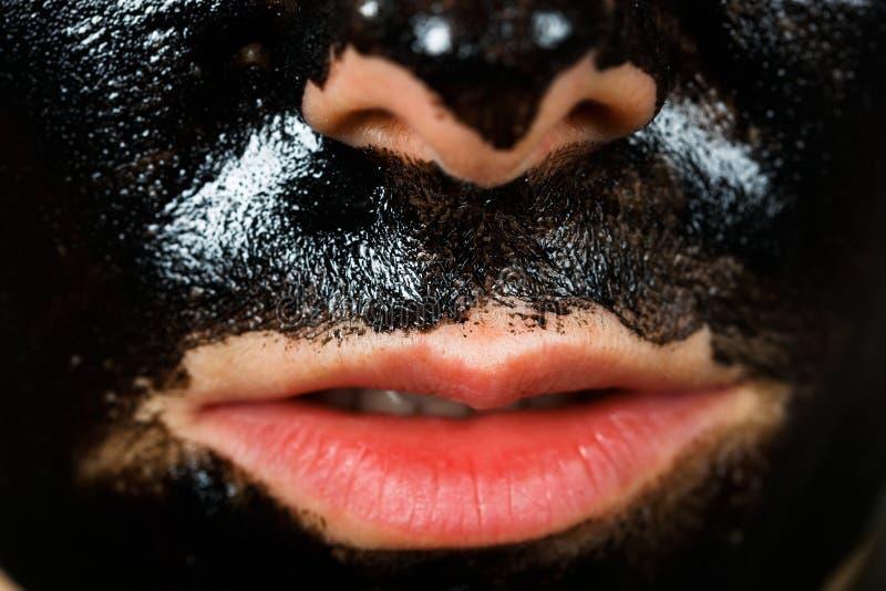 Facial black mask. Close up photo of young woman with facial black mask royalty free stock photo