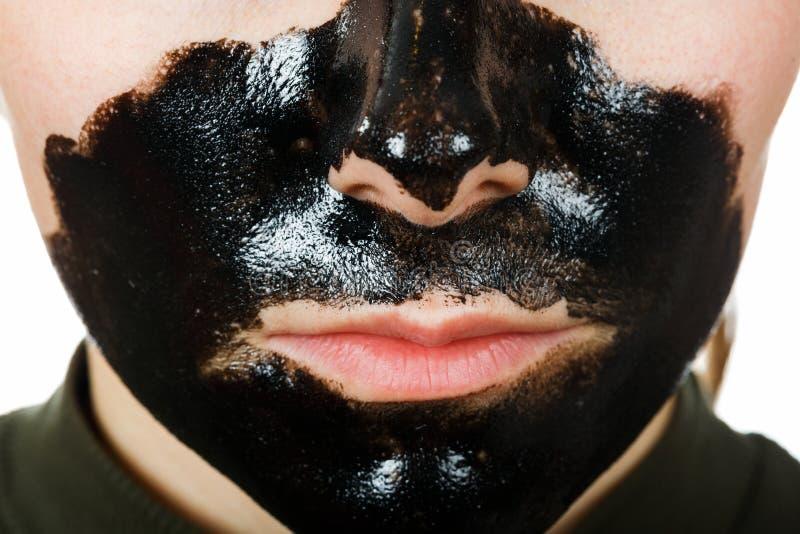Facial black mask. Close up photo of young woman with facial black mask stock image