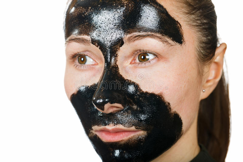 Facial black mask. Young woman with facial black mask on isolated white background royalty free stock images