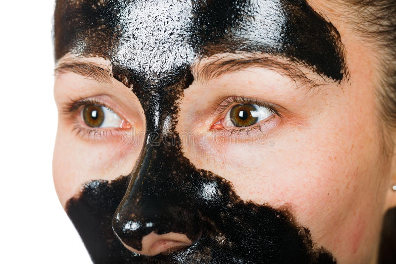 Facial black mask. Young woman with facial black mask on isolated white background royalty free stock photos