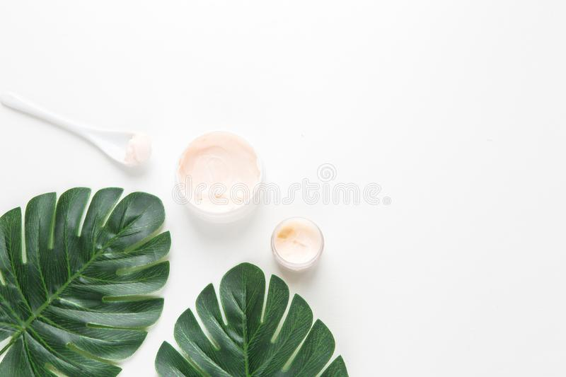 Facial and body spa. face cream on the background of tropical leaves of Monstera palm royalty free stock photos