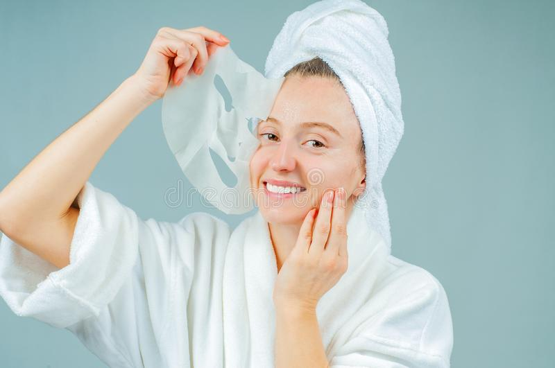 Facial care and beauty treatments. Beautiful woman with a sheet moisturizing mask on her face royalty free stock image