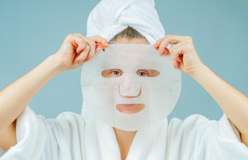 Facial care and beauty treatments. Beautiful woman with a sheet moisturizing mask on her face. Cosmetic procedure royalty free stock photos