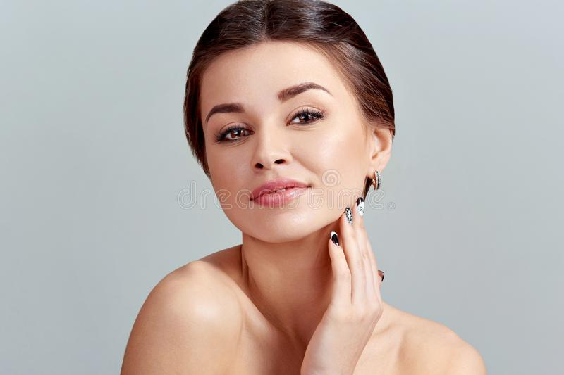 Facial Care. Female Applying Cream and Smiling. Beauty Face. Portrait Of Young Woman. royalty free stock images
