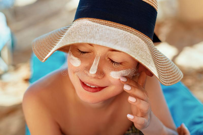 Facial Care. Female Applying Sun Cream and Smiling. Beauty Face. Portrait Of Young Woman in hat Smear Moisturizing Lotion on Skin. stock images