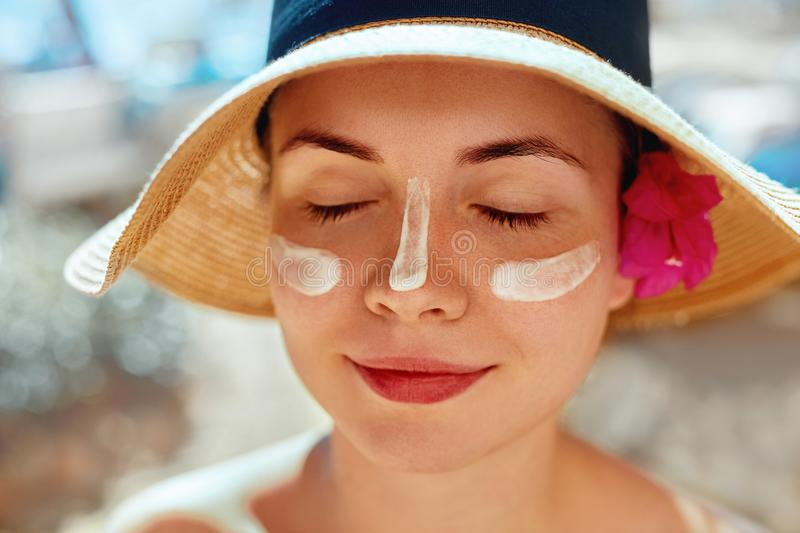 Facial Care. Female Applying Sun Cream and Smiling. Beauty Face. Portrait Of Young Woman Smear Moisturizing Lotion on Skin stock image