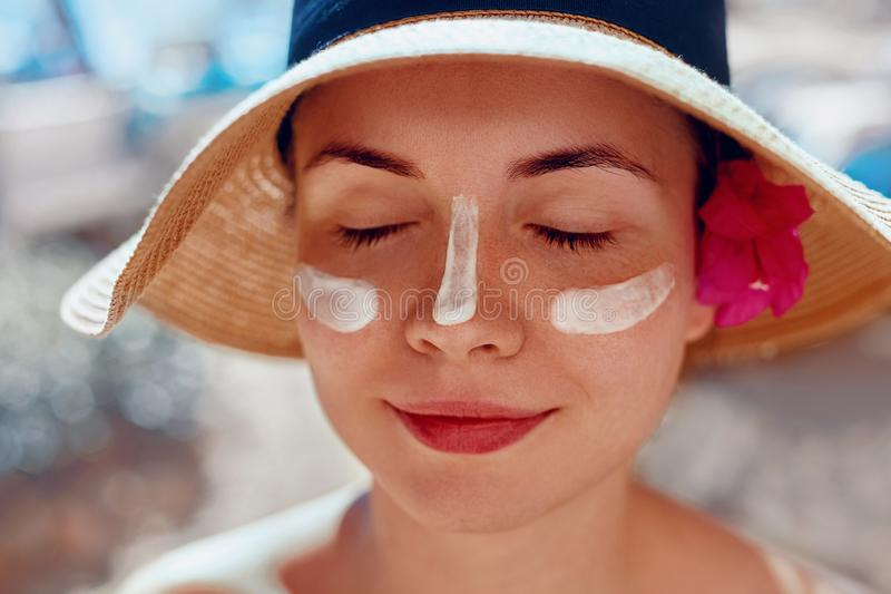 Facial Care. Female Applying Sun Cream and Smiling. Beauty Face.  Portrait Of Young Woman Smear  Moisturizing Lotion on Skin. SkinCare royalty free stock image
