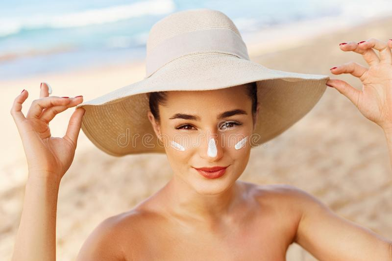Facial Care. Young  Female Holding Bottle Sun Cream and  Applying on Face Smiling. Beauty Face. royalty free stock photos