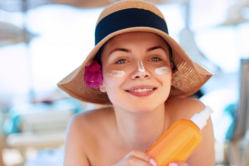 Facial Care. Young  Female Holding Bottle Sun Cream and  Applying on Face Smiling. Beauty Face.  Portrait Of Young Woman in hat Sm. Facial Care. Young Female royalty free stock photos