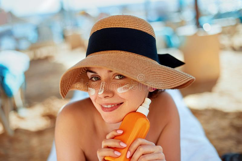 Facial Care. Young Female Holding Bottle Sun Cream and Applying on Face Smiling. Beauty Face. Portrait Of Young Woman in hat Smear Moisturizing Lotion on Skin royalty free stock photo