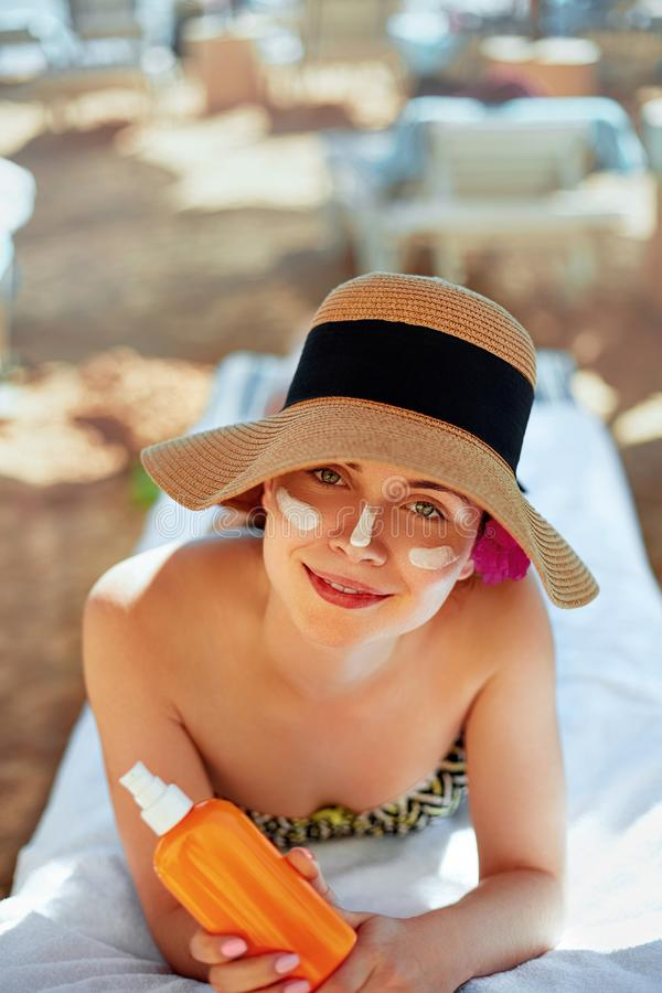 Facial Care. Young Female Holding Bottle Sun Cream and Applying on Face Smiling. Beauty Face. stock photo