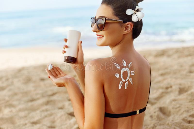 Facial Care. Young  Female Holding Bottle Sun Cream and  Applying on Face Smiling. Beauty Face.  Portrait Of Young Woman in hat Sm royalty free stock images