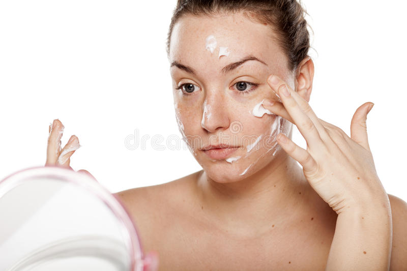 Facial care. Young woman applying cream on her face in front of a mirror royalty free stock photo