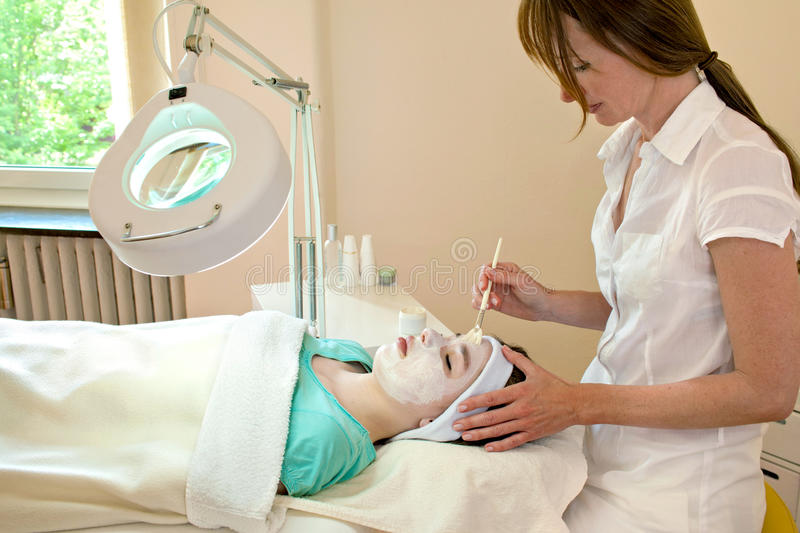 Facial Chemical Peel. Alternative practitioner applying a chemical peel to a female patient's face in a beauty clinic royalty free stock images