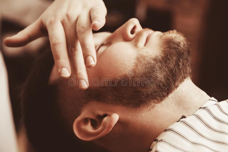 Facial close up. Applying lotion after shave in Barber shop royalty free stock photo