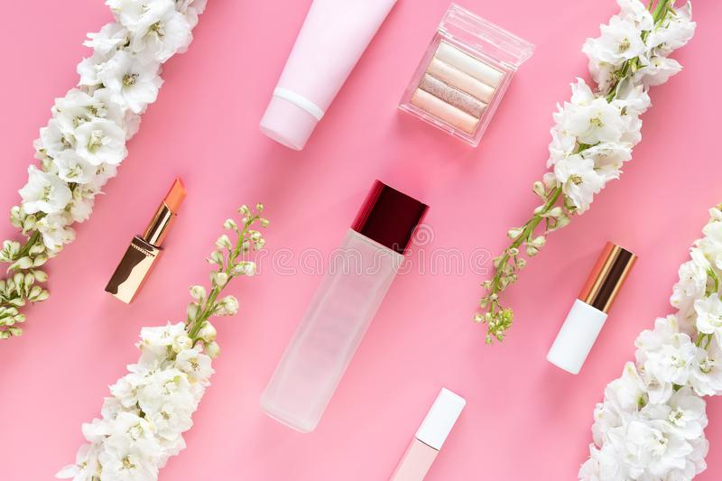 Facial cosmetic beauty products with white flower on pastel pink desktop background. natural beauty skin care layout, top view. Flat lay stock image
