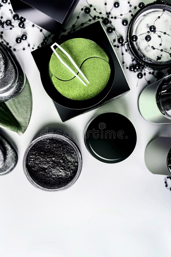 Facial cosmetic products setting in black and brown packaging. Natural cosmetics. Modern skin care with eye patches and charcoal. Powder on light background royalty free stock image
