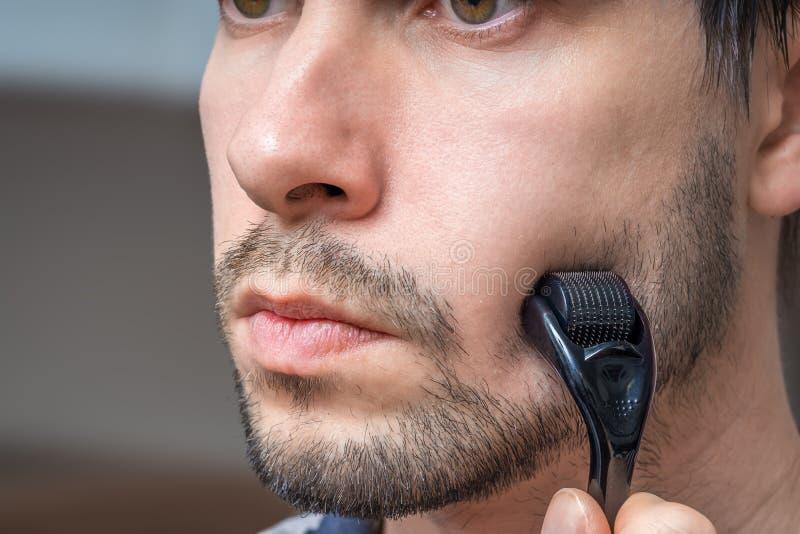 Facial hair care concept. Young man is using derma roller  on beard. stock photos