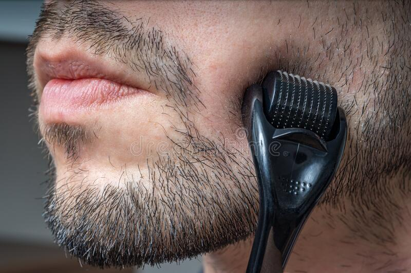 Facial hair care concept. Young man is using derma roller  on beard. stock photography