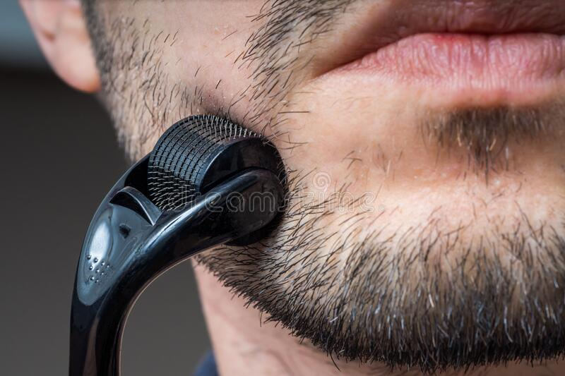 Facial hair care concept. Young man is using derma roller  on beard. royalty free stock photography