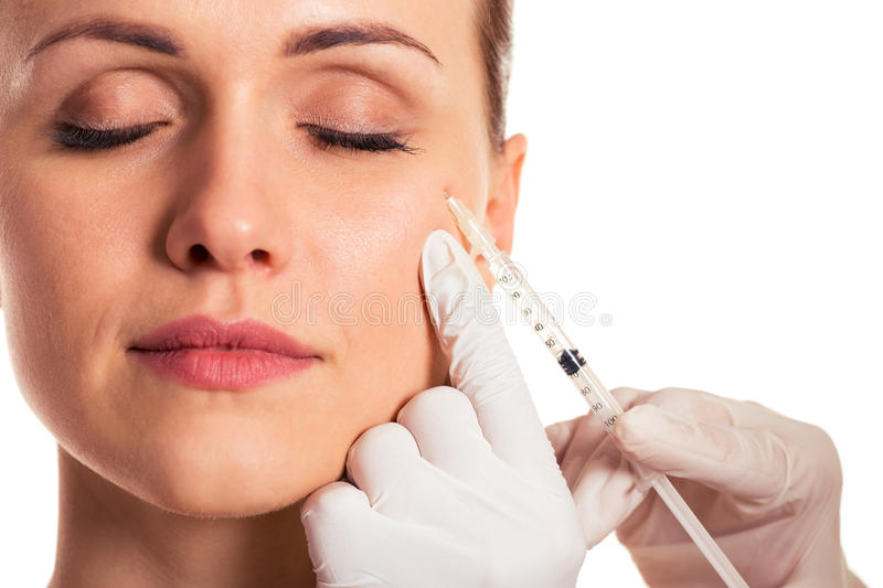 Facial injection for women. Beautiful woman with closed eyes, surgeon in medical gloves is making an injection in face, isolated on a white background, close-up royalty free stock photos