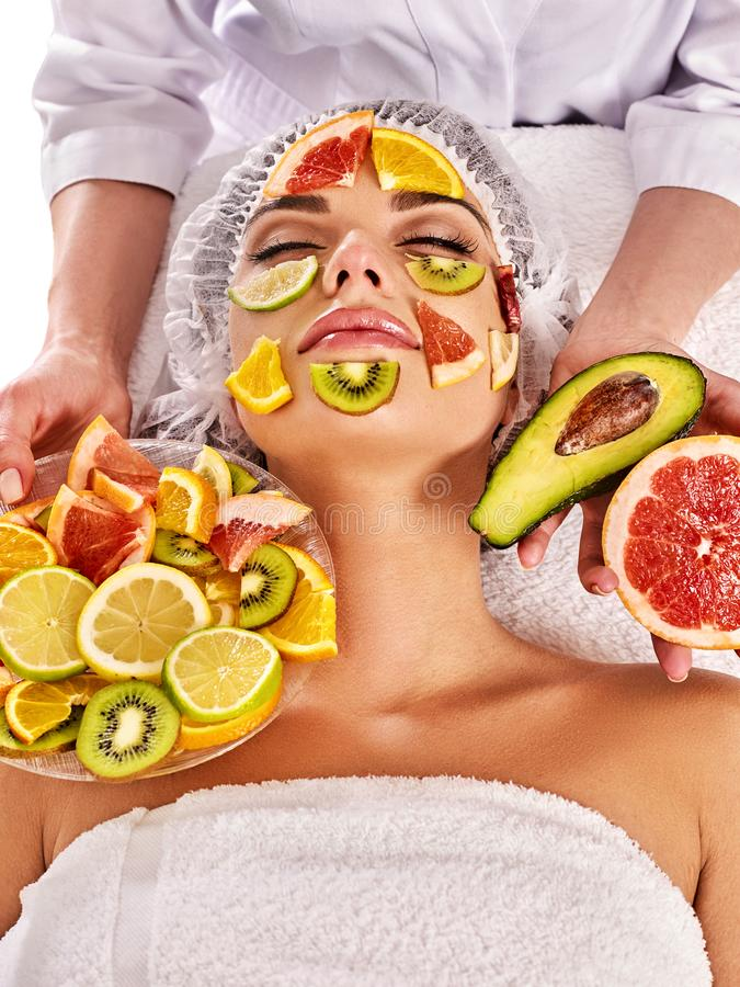 Facial mask from fresh fruits for woman . Beautician apply slices. stock photo