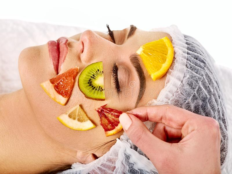 Facial mask from fresh fruits for woman . Beautician apply slices. stock photography