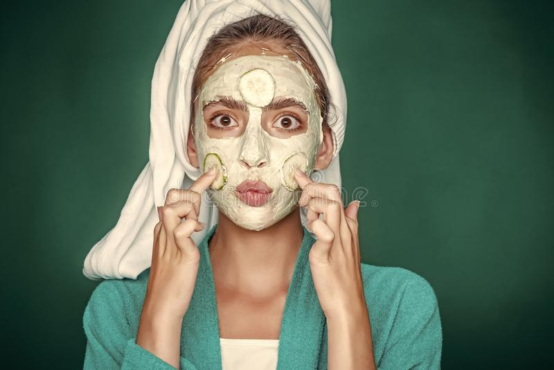 Facial mask. Girl face with kiss lips, cucumber mask on green background stock images