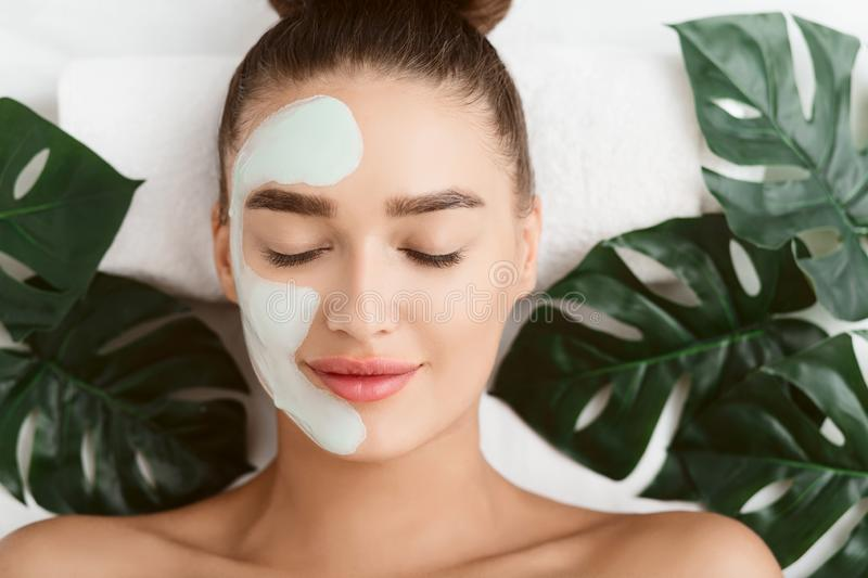 Facial Mask. Girl Lying On Table With Tropical Leaves stock photos