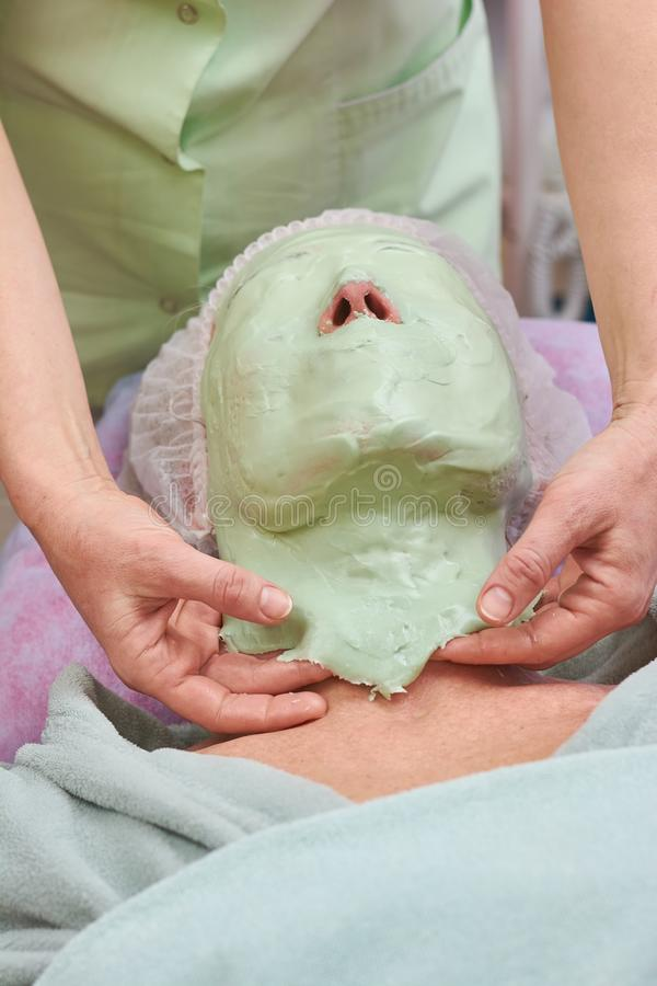 Facial mask, hands of cosmetician. Skin treatment in cosmetology clinic stock photography