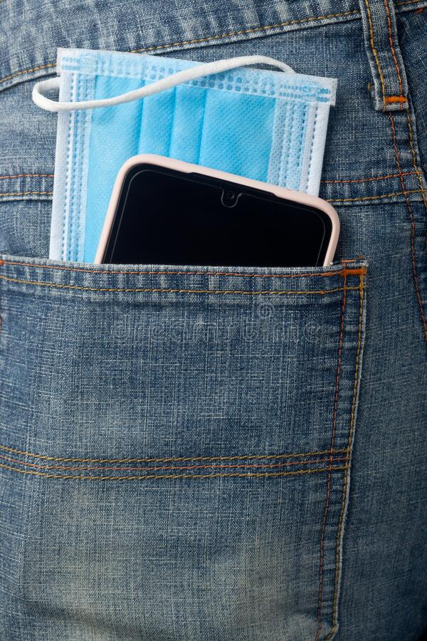 Facial mask and mobile phone in back pocket stock photos