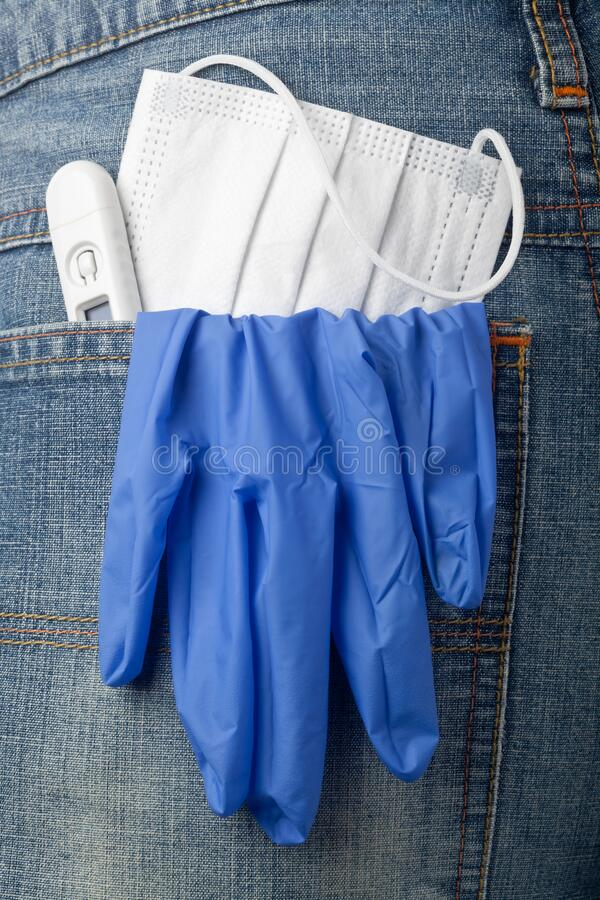 Facial mask, thermometer and latex glove in back pocket stock photography